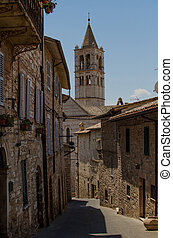 A medieval street in Assisi with view on the tower of Basilica of Saint Clare, by day. Italy