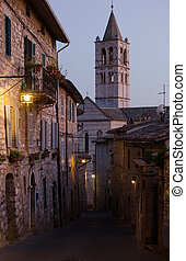 A medieval street in Assisi with view on the tower of Basilica of Saint Clare, by night. Italy
