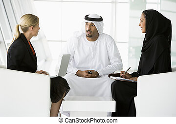 A meeting between a Caucasian businesswoman and a Middle...