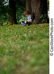 a, menino, senta-se, tendo, pernas cruzadas, perto, um, árvore grande, em, park.