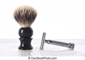 A mens razor and shaving brush on a wet bathroom counter top. The brush is standing and the razor on its side and covered with water drops.