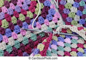 crochet - A metal crochet being used to make a colorful...