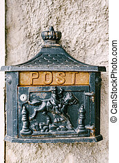 A metal mailbox with a horse rider on the wall of the house.