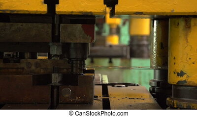 A metal rope moves slowly in a forging press in a workshop at a plant