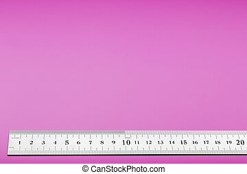 A metal ruler with a scale on a pink background is a superscape with a copy of the space for your text.