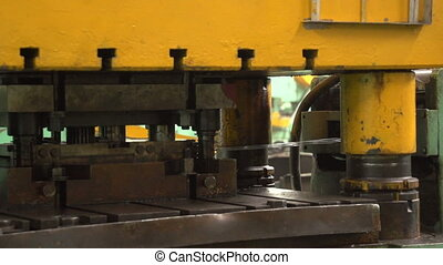 A metal string moves slowly in a forging press in a workshop at a plant