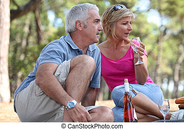 a mid age couple having a picnic in a pine forest