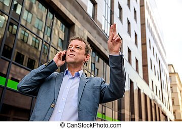 A middle age businessman waving for taxi