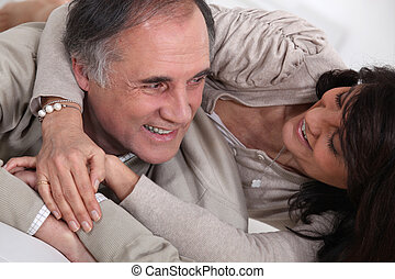 A middle age couple fooling around in bed.