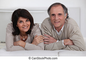 A middle age couple laying on their bed.