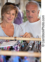 A middle age couple shopping for clothes.