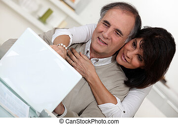 A middle age couple with a laptop.