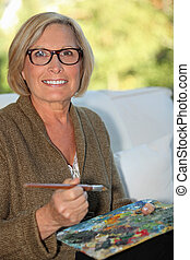A middle age woman painting.