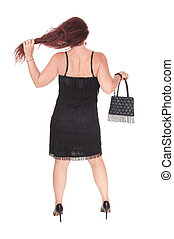 A middle age woman standing from the back in a black dress