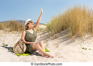 A middle-aged blonde woman sitting on the sand of a dune on the beach waving to someone