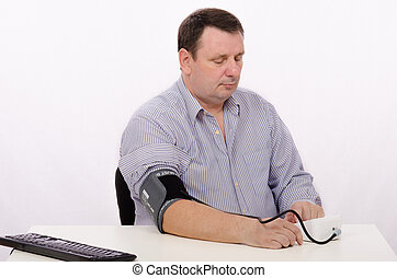 A middle aged man checks his blood pressure