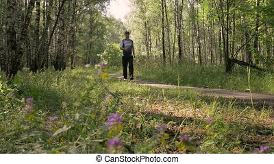 A middle-aged man, doing sports. He goes for a walk in the woods. Leads a healthy lifestyle.