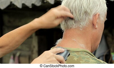 A middle aged man dressed in a khaki t-shirt, shaving by woman with a clipper.