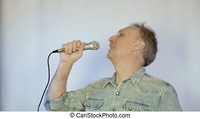 A middle aged man sings into a microphone. He has a great...