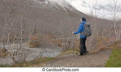 A middle aged man travels a mountain path with a backpack....