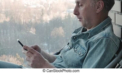 A middle aged man uses a smartphone. He is studying various...