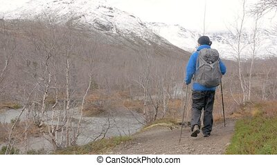 A middle-aged man walking along a mountain path with a backpack. He travels and leads a healthy lifestyle.