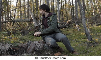 A middle aged man with a beard on a tree stub takes a picture of the surrounding environment with a smartphone, putting the smartphone off, getting up and walking away.