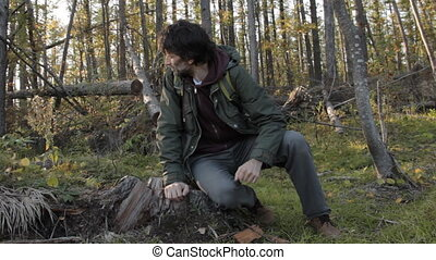 A middle aged man with a beard on a tree stub taking out a smartphone, blowing an insect off his hand and takes a picture of the surrounding environment.