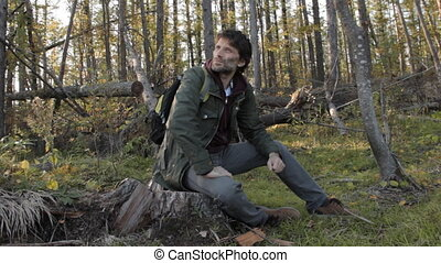 A middle aged man with a beard wearing grey pants, green jacket and yellow boots lit be the setting sun having rest on a tree stub, looking around, getting up to walk on.