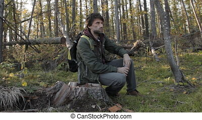 A middle aged man with a beard wearing grey pants, green jacket and yellow boots on a tree stub taking breath, taking out a plastic bottle, having a sip and putting it back.