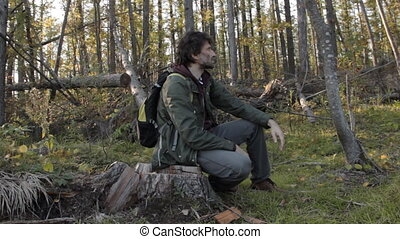 A middle aged man with a beard wearing grey pants, green jacket and yellow boots on a tree stub brushing off the annoying insects, getting up and walking on.