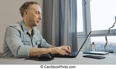 A middle aged man working on a laptop. Freelancer works at ...