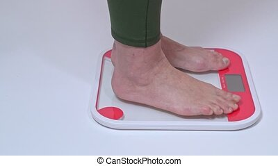 A middle-aged obese woman stands on the scales for weighing ...