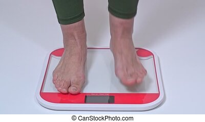 A middle-aged woman stands on the scales for weighing with her bare feet