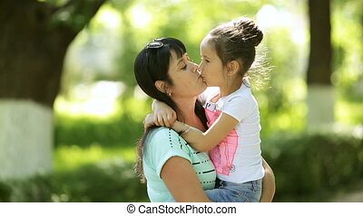 A middle-aged woman hugs and kisses her daughter, holding her in her arms. Outdoor