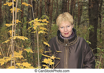 A middle-aged woman in autumn forest