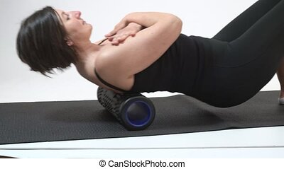 A middle-aged woman is doing a backbone massage on myofascial roller. Close-up