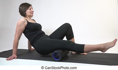 A middle-aged woman on a gymnastic mat with myofascial roller does an exercise on her hips on a white background