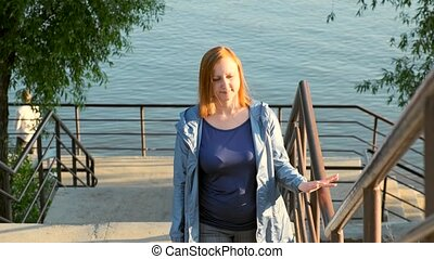 A middle aged woman walks up the stairs from the riverbank