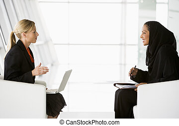 A Middle Eastern and caucasian woman talking at a business...