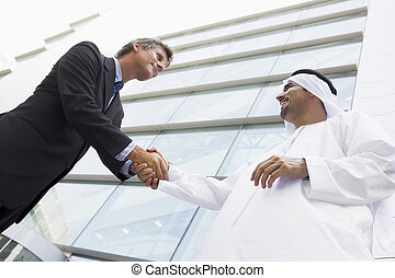 A Middle Eastern businessman shaking hands with a Caucasian busi