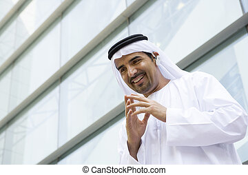 A Middle Eastern businessman standing outside an office block ta