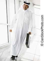 A Middle Eastern businessman walking in a corridor