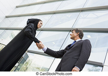 A Middle Eastern businesswoman and a Caucasian man shaking hands