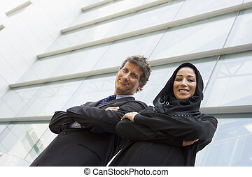 A Middle Eastern businesswoman and a Caucasian man standing outs