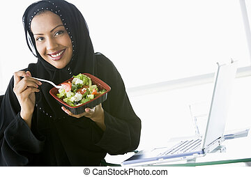 A Middle Eastern businesswoman eating salad beside her laptop