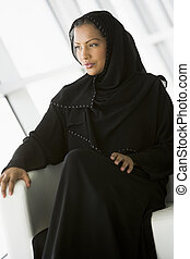 A Middle Eastern businesswoman sitting in a chair