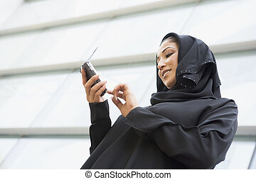 A Middle Eastern businesswoman using a PDA