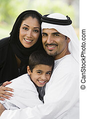 A Middle Eastern couple and their son sitting in a park