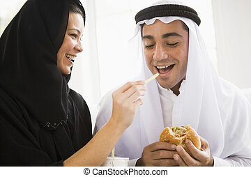 A Middle Eastern couple sharing a fast food meal